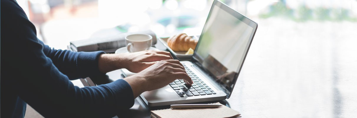 photo of a man writing on a laptop